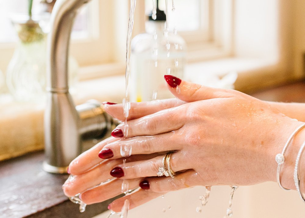 hands washing at a sink with rings and bracelets on